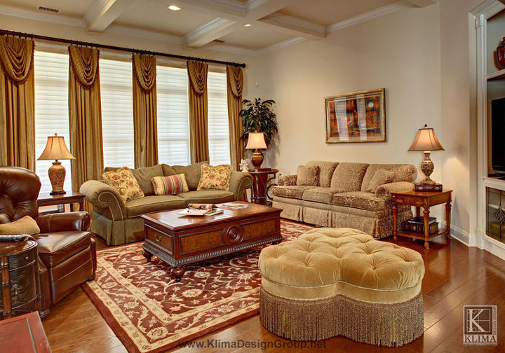 Layers of fine reproductions furnishings add old-world comfort. Drapery panels with casual swags highlight the height of the room as they extend upward and draw attention to the coffered ceiling.