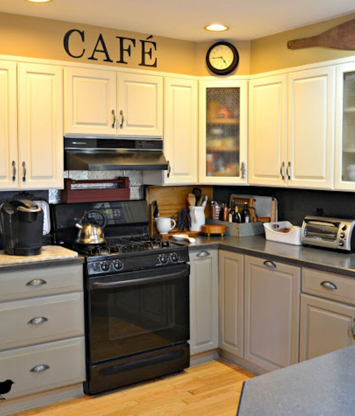 Black countertops and black and stainless appliances compliment the grey and white cabinets.