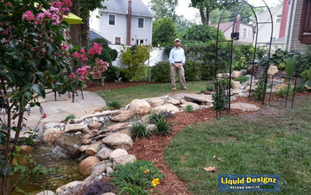 A tranquil meandering stream and koi pond grace this small backyard.