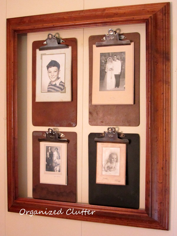 Four old clipboards with black and white vintage photos in vintage folders, hang inside a frame.