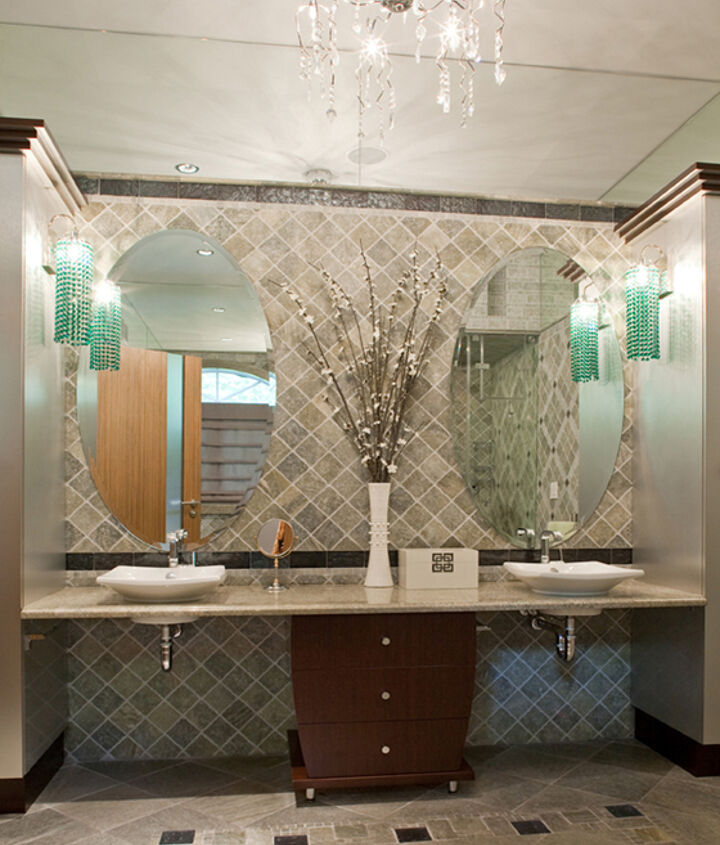 This modern bathroom features designer's bathroom tile designs. It is all about artful manipulation of inexpensive materials, including natural stone, glass and metal tiles. The style is modern classic where there is little distinction