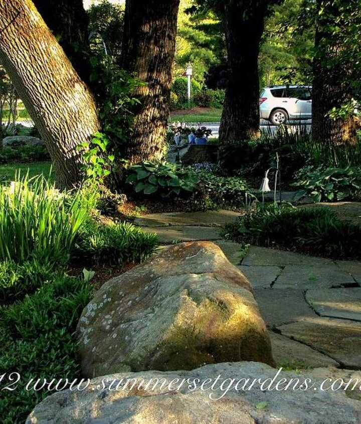 A simple, rustic stepping stone path leading from the upper patio through a shade garden to the front yard. I randomly place weathered boulders into the planting beds. Some of the plant groupings are Liriope, Hosta, Iris, Lamium, Ajuga