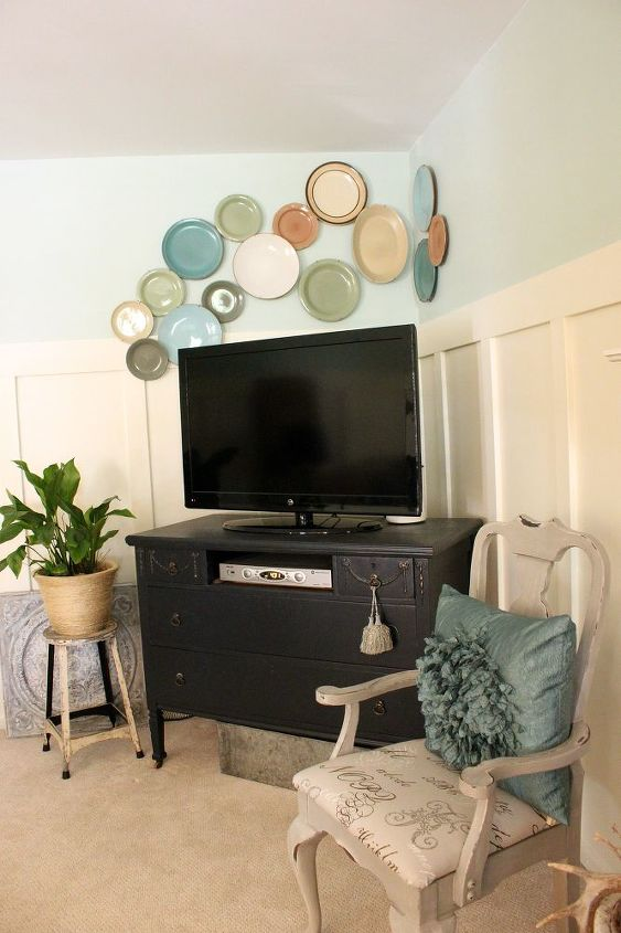 free form plate wall and old dresser from yardsale holding the tv. vintage stool and painted side chair.