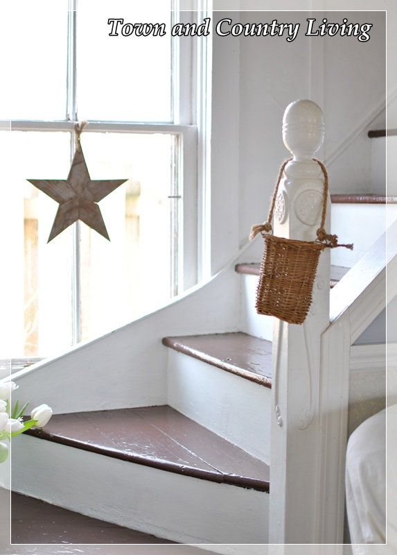A simple wooden star adds interest to the window oddly placed at the bottom of the stairway.