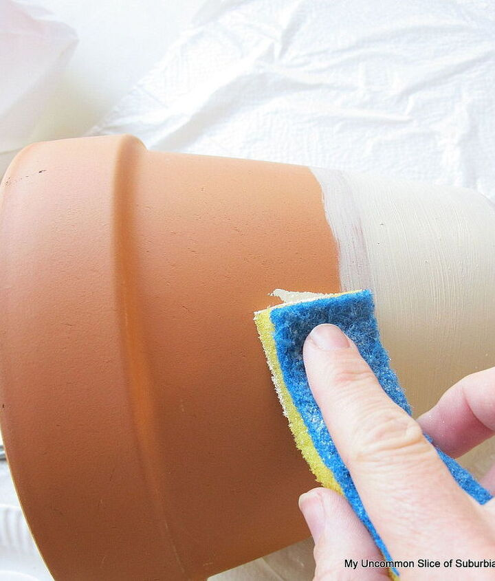 Take a sponge and apply the paint mixture onto the terra-cotta pot leaving certain areas of the pot lightly exposed.