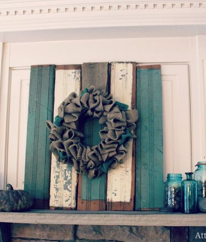 Fall mantel featuring aburlap wreath on chippy blue and cream vintage salvaged wainscoting, pumpkins and vintage blue Ball jars
