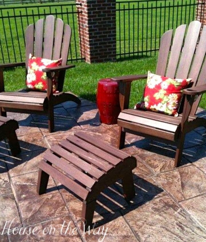 Adirondack chairs with floral pillows and outdoor garden seat used as an end table.