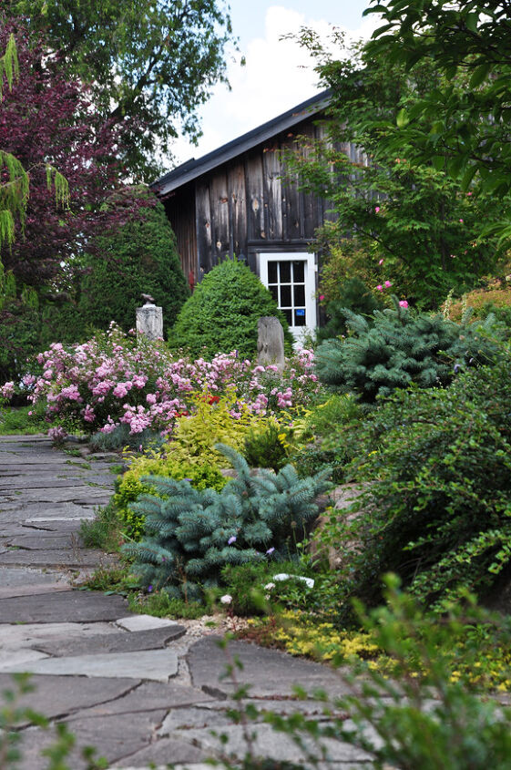 At the front of the house there is a flagstone courtyard filled with romantic pink roses. A set of stone steps leads you down and into the little courtyard.