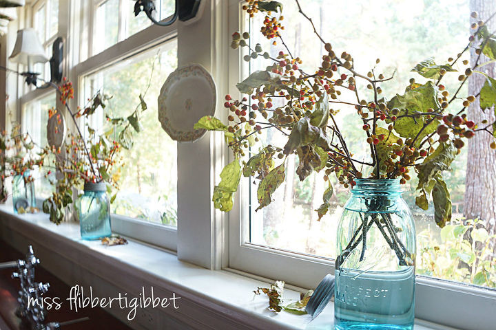 My kitchen windowsill...blue Mason jars with bittersweet