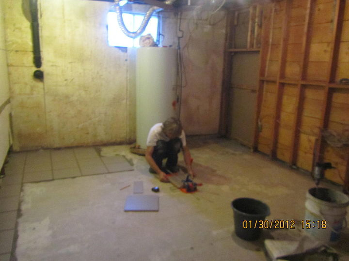 dividing a storage room to storage in the back, bathroom in the front  My brother putting tiles down