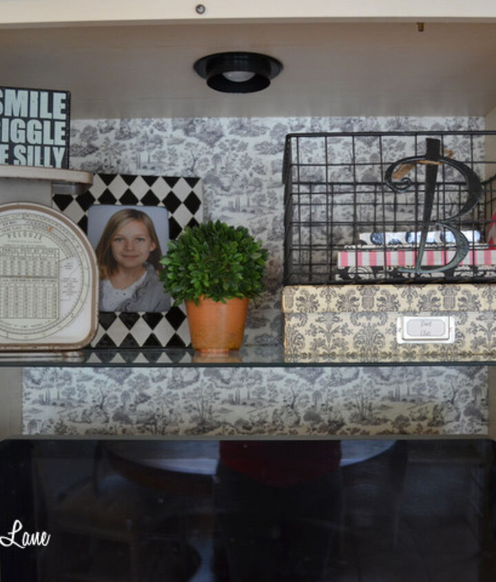 """Using scrapbook paper and spray glue, I """"wallpapered"""" the back of the armoire in a black and white toile print to add visual interest."""