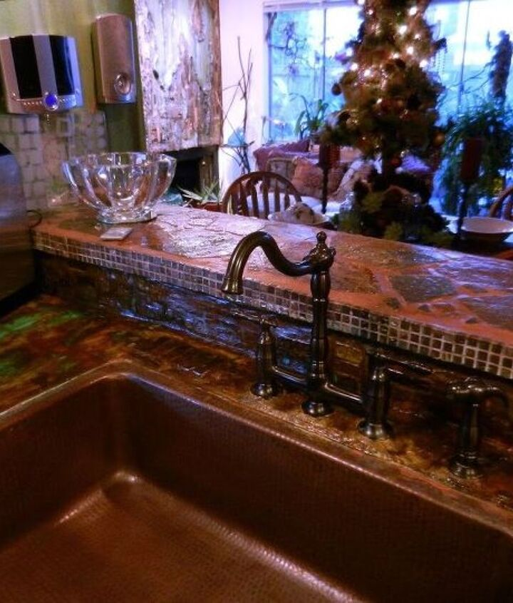 Resurfaced countertops with mesh rewire and applied cement to surface.  Colored with concrete acid stain.  Dropped in copper apron sink and bridge faucet.  The stone work on countertop and stove backsplash is standard patio stone.