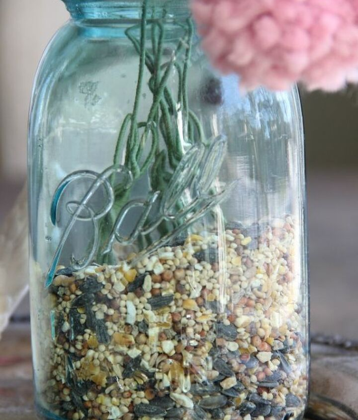 Birdseed as an unusual vase filler!   http://eclecticallyvintage.com/2013/01/how-to-make-a-pom-pom-flower-bouquet-with-a-fork/
