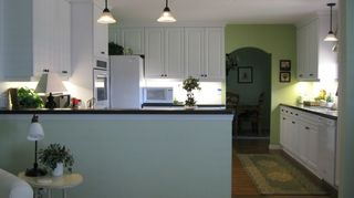 q i am going to be remodeling a kitchen in a little home in florida soon, home decor, home improvement, kitchen design, After Light bright and white Removing the beams from the ceiling and taking the cabinets all the way to the ceiling made the 8 ft ceiling seem much higher Some minor layout changes were also made to improve function