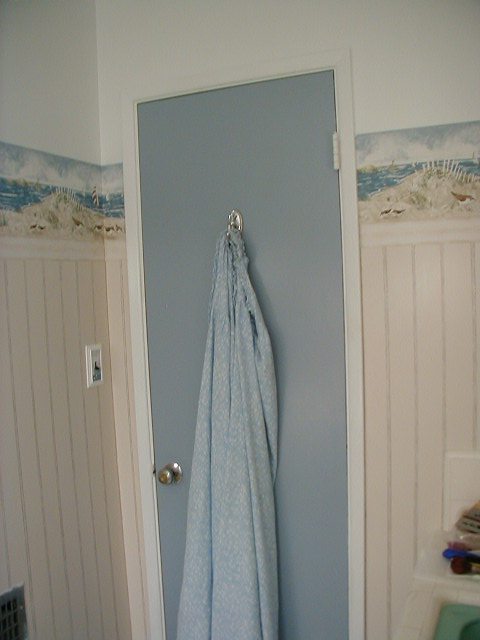 It was cheaper just to paint the old door to match the vanity and it helped balance the design. I added a chrome hook to match all the new towel racks and hardware.