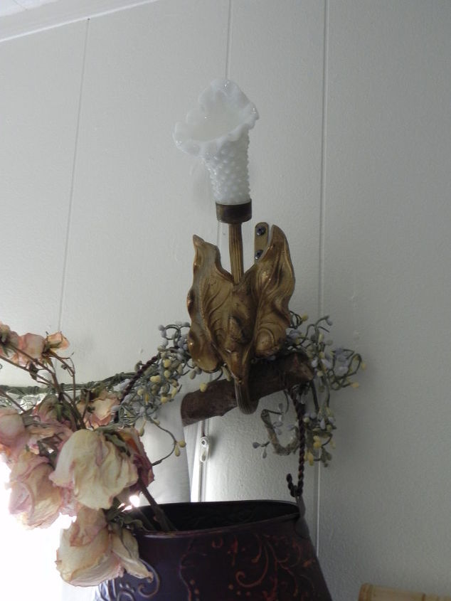 small touches like hanging the branch from vintage milk glass curtain holders and adding a metal basket and beaded vine