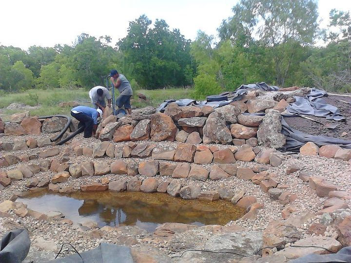 The pond has been rocked and is filling with rainwater.  Now the fun part--building the waterfall.  We only had a machine with a bucket, so we had to be careful.  If we set a heavy boulder in the wrong place, we couldn't move it later!