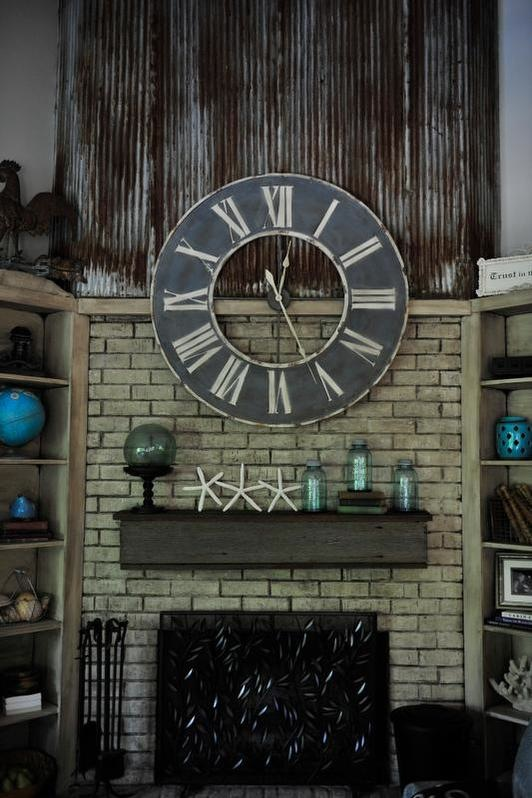 Fireplace makeover by Bella Tucker Decorative Finishes using an old rusty tin roof and a barn wood mantle.
