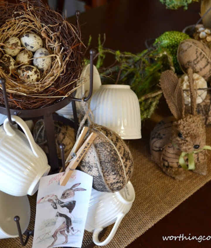 In addition to the nest and printed images, there are burlap covered eggs hanging from the mug tree.