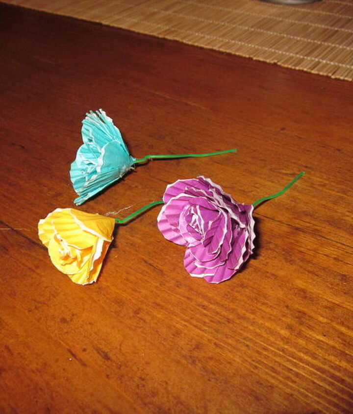 Small multicolored cupcake liners wrapped around a small green colored paperclip, attached with hot glue.
