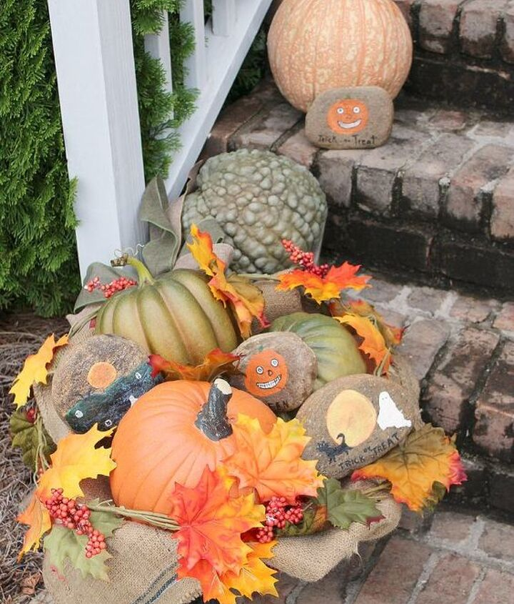 Fall Front Porch Decor vignette created in a vintage metal child's wheelbarrow. I nestled rocks handpainted with Halloween scenes in with pumpkins and fall foliage.