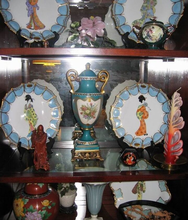Looking inside her cabinet that displayed a few of the 12 China plates she painted & fired in her kiln. Also painted the blue/gold vase. Others items were bought.
