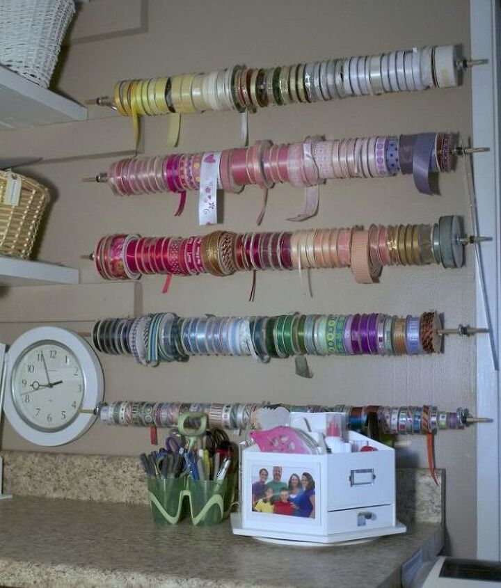 Five wooden dowel rods 1/4 inch thick, as the individual ribbon rolls demanded. We hooked off the ends with a washer and hung them up with a eye bolt. Easy and pretty to look at. I tried to organize according to color families.