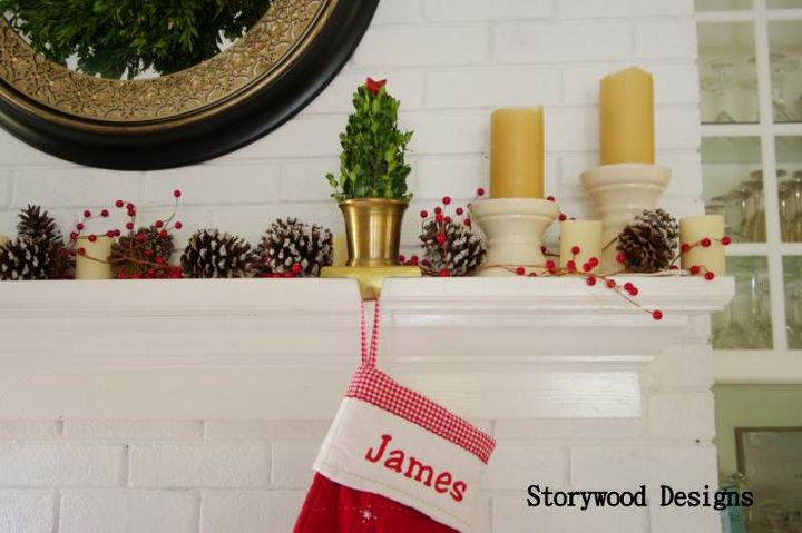 Boxwood Christmas trees sit in cache pot stocking holders among flocked pine cones, holly berries and candles.