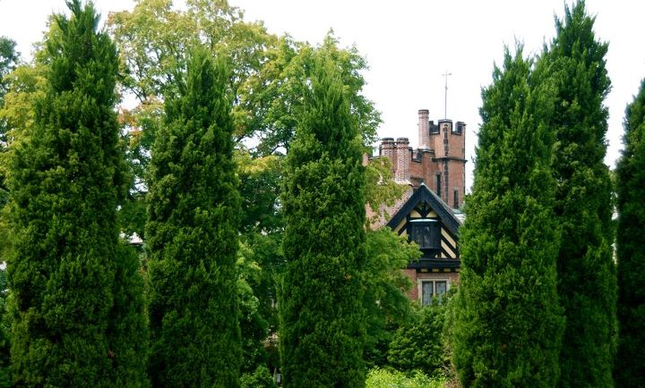 An unusual sight in Ohio: Stan Hywet Hall stands in its Tudor splendor as framed by the pillar shrubs of the Elliptical Garden. This garden can be seen walking from the Great Garden to the Carriage House, which is the official visitor