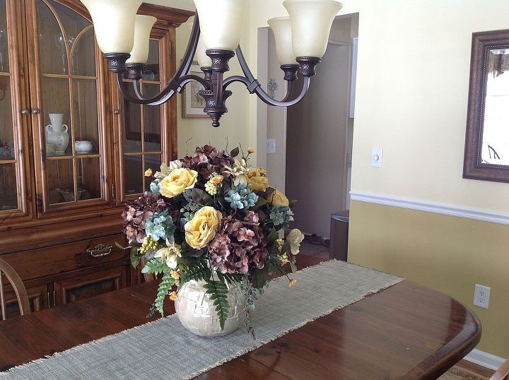 After: A custom designed silk floral arrangement, table runner and wall mirror finish off the room.
