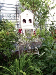 fence piece upcycled as trellis, step ladder supports a birdhouse and planter