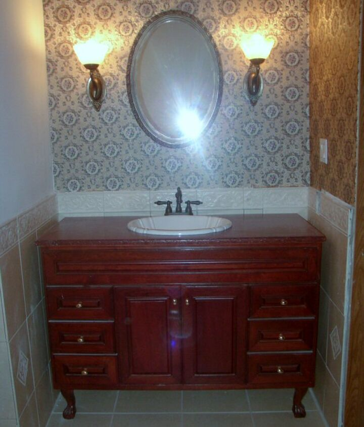 """This is the sink area- the claw foot vanity we made out of a damaged cherry cabinet my husbands work was going to pitch after the forklift damaged it. We fixed it and custom ordered the cherry wood top and treated with spar poly urethane and trimmed it out with molding and attached feet and I stained it all to match. The bowl and faucet were clearance items- $20 and $25 respectively. The mirror I picked out of someones trash and ordered the swan sconces in chrome on ebay for $5 each...painted and used rub n buff to antique them. The alabaster shades I will someday change out when I find ones I like better that are taller. I got those for $3 each. You can see some of the grout on the tiles here too...I did get the """"swirls"""" scrubbed off."""