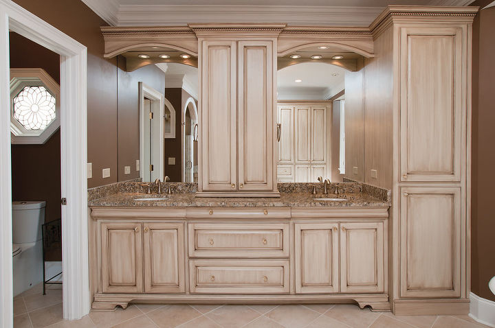 To the left are the his and her's vanity cabinetry and sinks. The rope moulding along with the arches look great on the antiqued finished cabinetry. Each sink in the bathroom has its own point of use water heater for instant hot water. There is no waiting for the hot water to come in this bathroom.