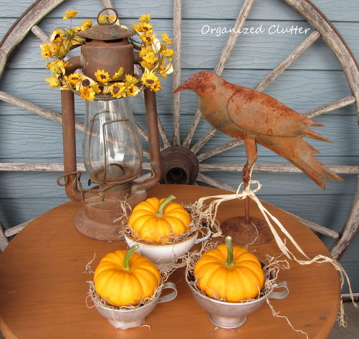 Canning funnels, mini pumpkins and a rusty lantern and crow on the crock table.