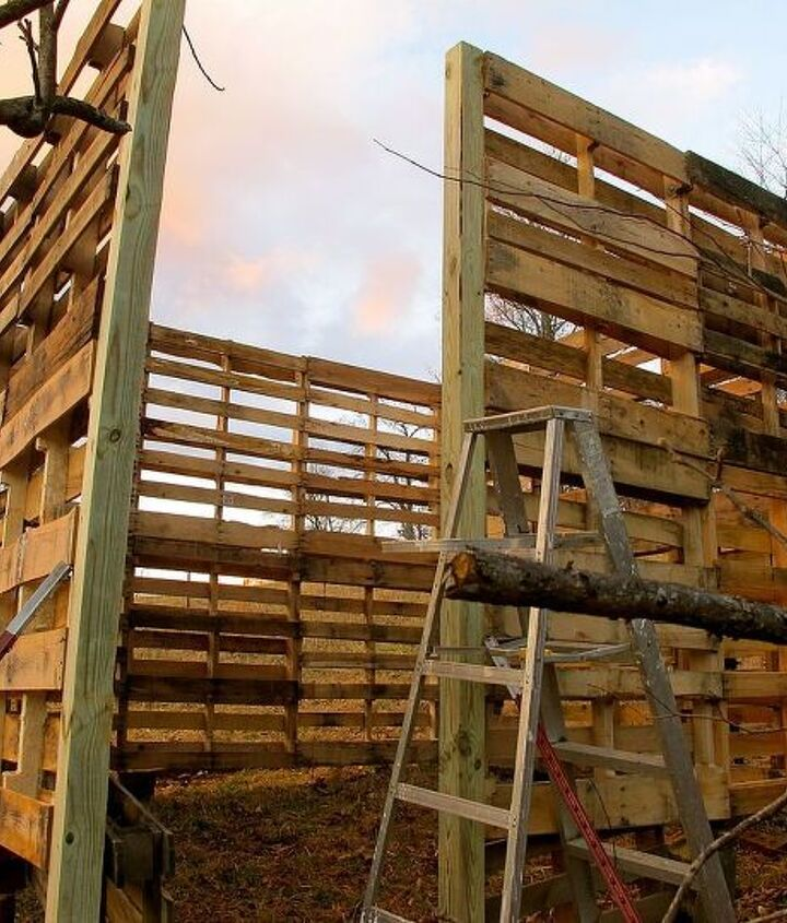 The corner posts are treated 4x4s. They are anchored to the ground and help to support the 2nd story of pallets.