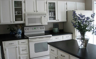 80 s tract home kitchen makeover, countertops, diy, home decor, kitchen cabinets, kitchen design, painted furniture, We used the Rustoleum Countertop Transformation Kit to update her formica butcher block counters We painted all the cabinets white added glass doors for interest and used new nickel hardware
