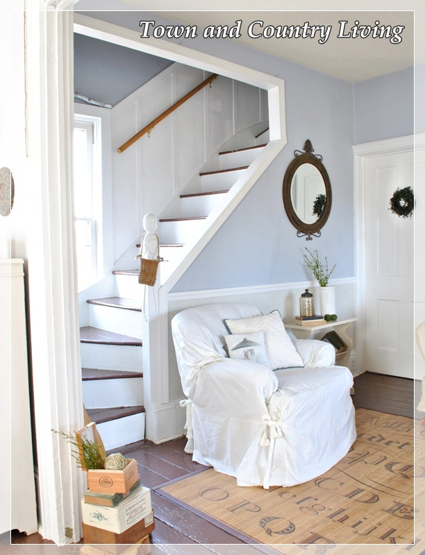 A club chair provides comfy seating along a wall wedged between the staircase and laundry room door.