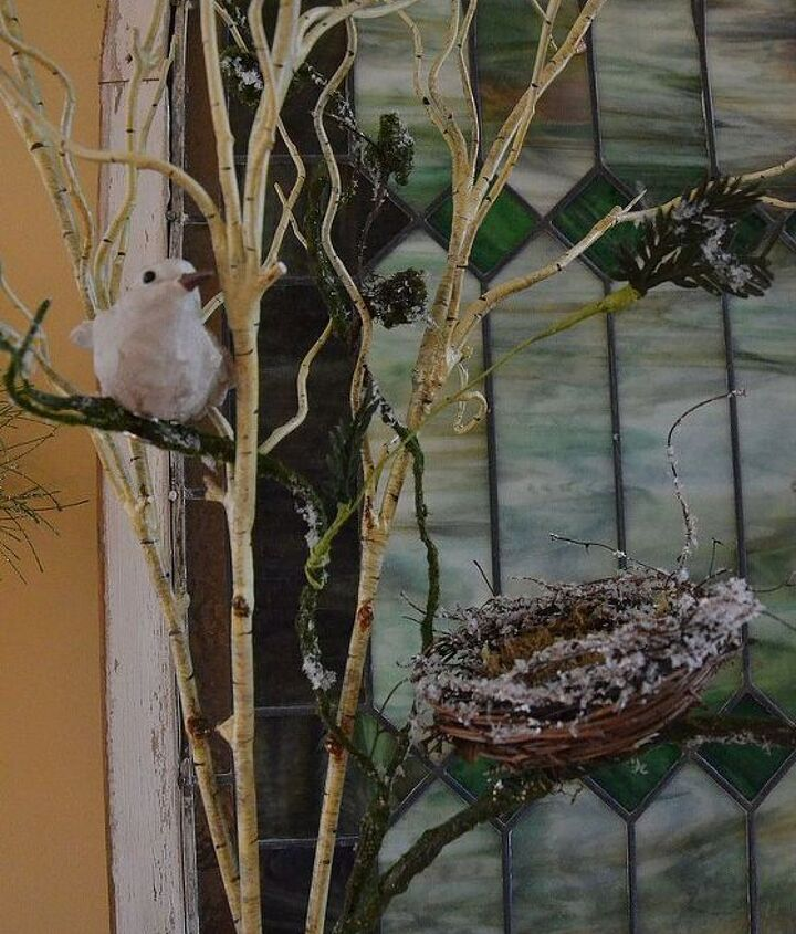 Birds perched on branches in front of stained glass