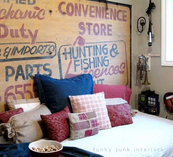 An old grocer's sign became a whimsical wall element behind a daybed for a playroom. Coordinate bedding with the sign graphics and call it done.  Visit post at: http://www.funkyjunkinteriors.net/2009/11/one-funky-playroom-reveal.html