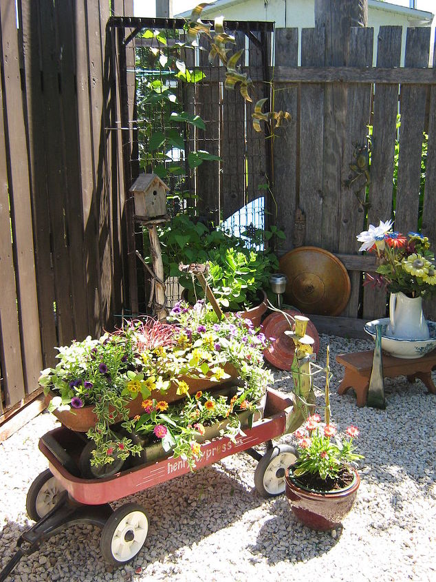 Old forgotten wagons with a new life as adorable planters( I least I think they're lovely!) sit in front of a bedspring trellis. The mirror behind the trellis is from a closet door!