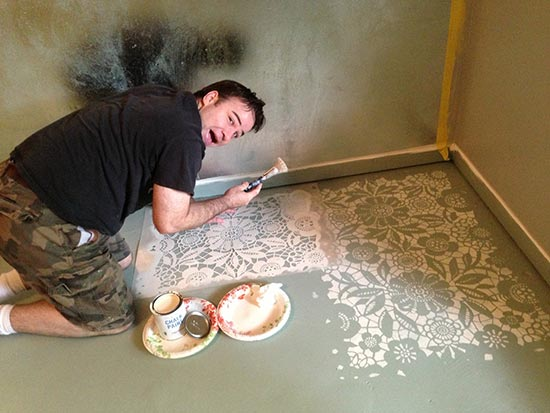 Brook of Bella Tucker Decorative Finishes in process on his stenciled floor transformation.