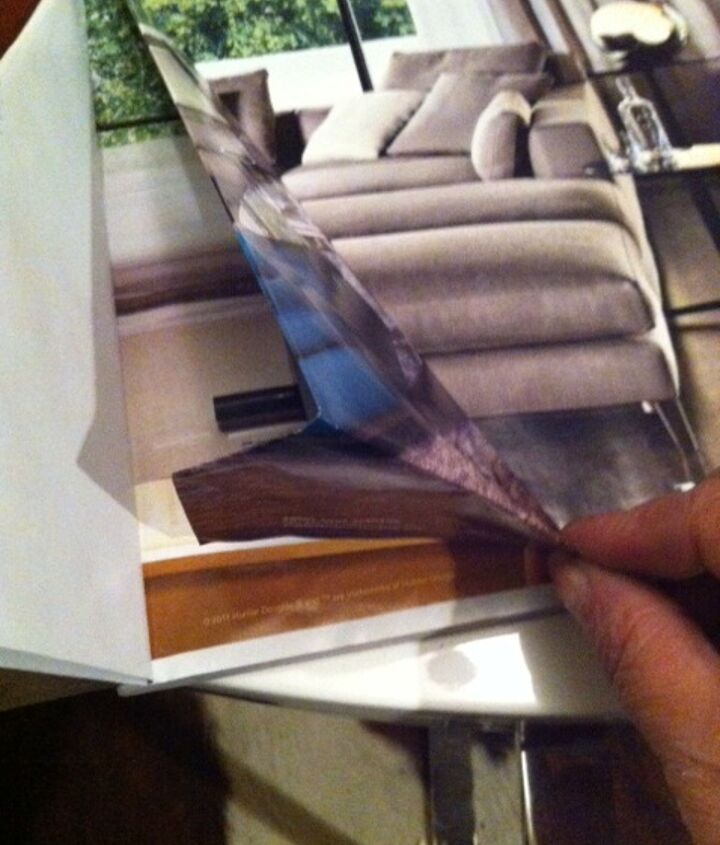 """Take the """"tail"""" that is hanging longer than the magazine, and fold it under, tucking it in between the folds you have made."""