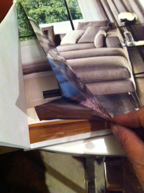 "Take the ""tail"" that is hanging longer than the magazine, and fold it under, tucking it in between the folds you have made."