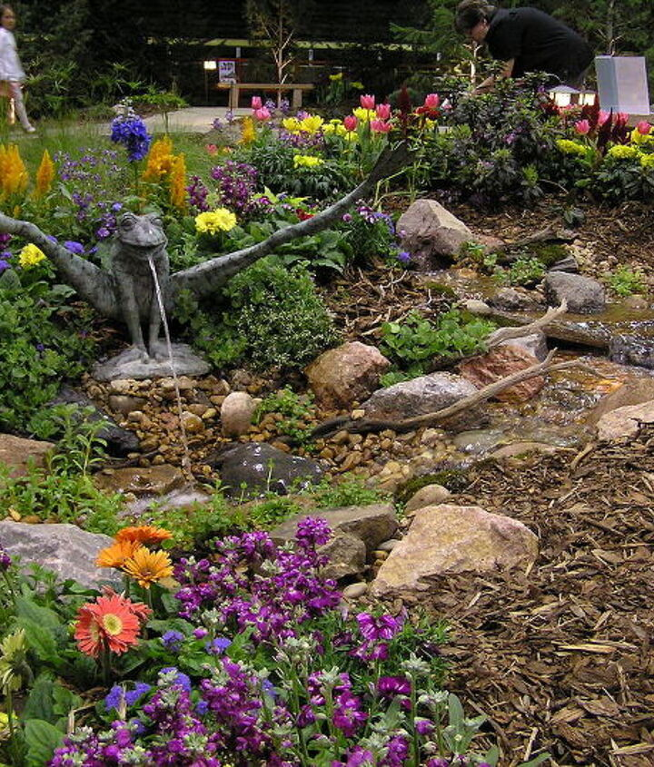 A frog spitter adds a bit of whimsy to this pondless waterfall.