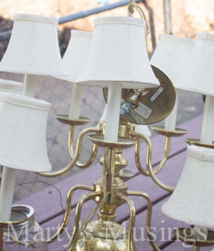 Throw away 10-light brass chandelier with cloth shades.