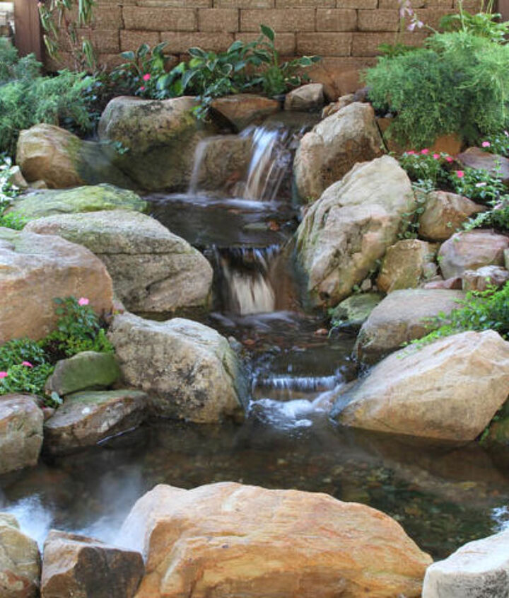 This small pond and waterfall is tucked beside a patio situated under a deck. A great solution for a spot that was once an eyesore.