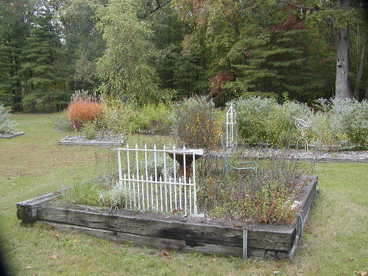 Our raised herb bed in front with meadow boarder in the rear. One of five birdbaths provide water for the birds.