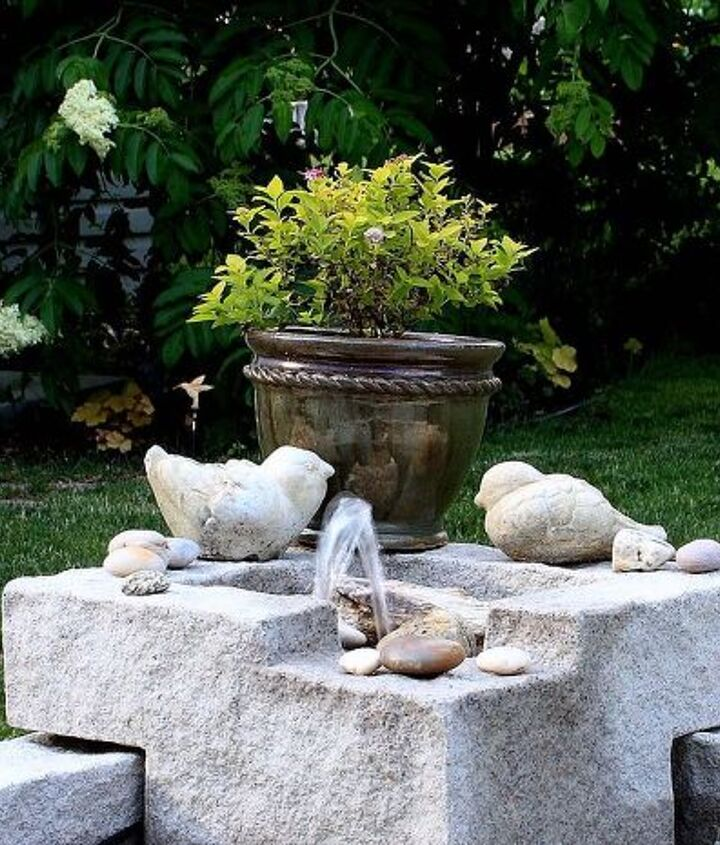 Fountain decorated with colorful stones and plants.