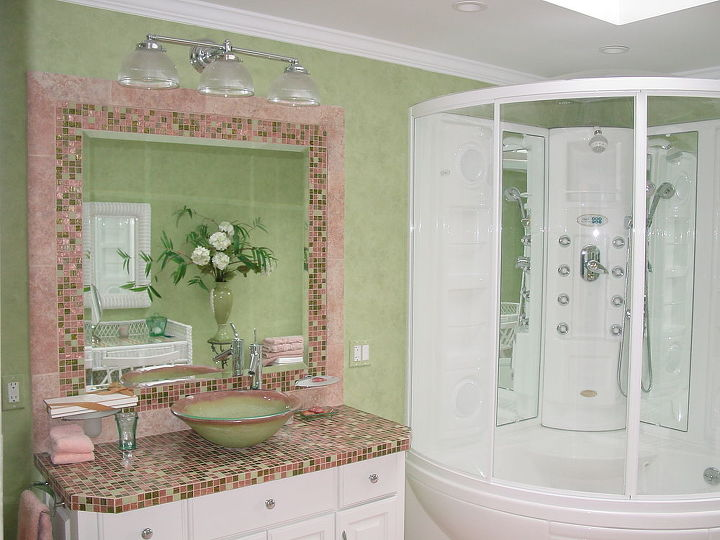 Custom cabinets with Bisazza tile countertop and mirror frame complimented with polished chrome fixtures.