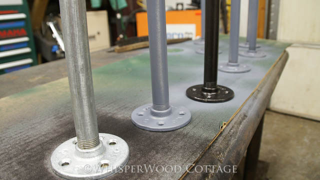 We started with this metal flanges, rods, and tips, coated them with primer, and then coated them with a layer of oil-rubbed bronze spray paint.
